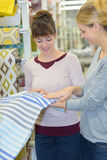 Portrait two women holding piece fabric in store stock images