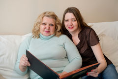 Portrait of two women with a photo album. Mother and daughter. Royalty Free Stock Photography
