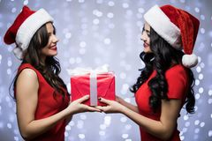 Portrait of two women in santa hat and red dress with gift in hands look each other on bokeh light background. Winter holiday Chri. Portrait of two women in Royalty Free Stock Image