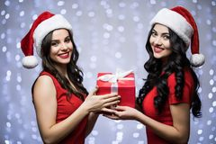 Portrait of two women in santa hat and red dress with gift in hands look on camera on bokeh light background. Winter holiday Chris. Portrait of two women in Stock Photo