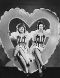 Portrait of two women sitting in large heart Stock Images