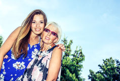 Portrait of two women in the summer outdoors. Mother and daughter hugging. Grandmother and granddaughter. Royalty Free Stock Images