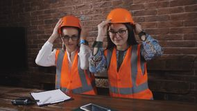 Portrait of two women at the table wearing safety helmets in the construction office.