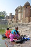 CHITTORGARH, RAJASTHAN, INDIA - DECEMBER 13, 2017: Portrait of two women washing clothes and dressed with colorful saris with Rata royalty free stock images