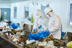 Trash Sorting on Waste Processing Plan. Portrait of two workers  wearing biohazard suits and hardhats working at waste processing plant sorting recyclable Royalty Free Stock Image