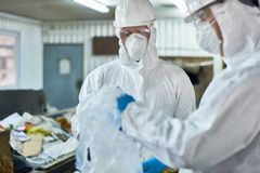 Workers Sorting Recyclable Materials. Portrait of two workers wearing biohazard suits sorting recyclable plastic and cardboard  at waste processing plant Stock Photo