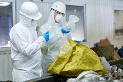 Workers Sorting Plastic on Trash Recycling Plant. Portrait of two workers wearing biohazard suits working at waste processing plant sorting recyclable plastic on stock photos