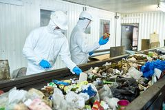 Sorting on Waste Recycling Plant. Portrait of two workers  wearing biohazard suits working at waste processing plant sorting trash on conveyor belt, copy space Royalty Free Stock Image
