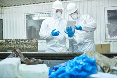 Workers at modern trash processing plant. Portrait of two workers wearing biohazard suits working at waste processing plant using digital tablet and sorting stock photo