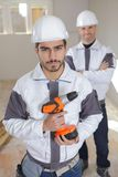 Portrait two workmen one holding cordless drill. Portrait of two workmen one holding cordless drill Royalty Free Stock Image
