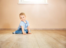 Portrait of a two years old child sitting on the floor. Pretty little boy at home Stock Images