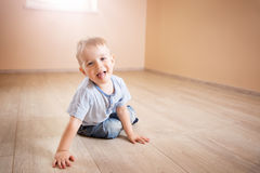 Portrait of a two years old child sitting on the floor. Pretty little boy at home Stock Photos