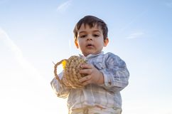 Portrait of two years old toddler holding bascet with two easter eggs - golden hour royalty free stock photo