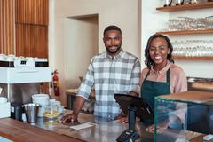 Smiling African entrepreneurs standing at the counter of their bakery. Portrait of two young African entrepreneurs smiling and standing welcomingly together royalty free stock image