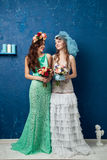 Portrait of two young attractive brides on blue background Royalty Free Stock Images