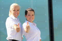 Portrait of two young attractive business women thumb up Stock Photography