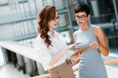 Portrait of two young attractive businesswomen talking on break Royalty Free Stock Images