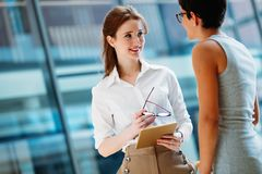Portrait of two young attractive businesswomen talking on break Royalty Free Stock Photo