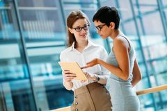 Portrait of two young attractive businesswomen talking on break Stock Images