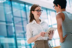 Portrait of two young attractive businesswomen talking on break Royalty Free Stock Photography