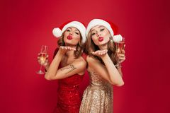 Portrait of two young attractive girls in christmas hats. And dresses holding champagne glasses and sending air kiss isolated over red background Royalty Free Stock Photo