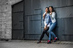 Portrait of two young and attractive women standing next to the wall. Royalty Free Stock Photography