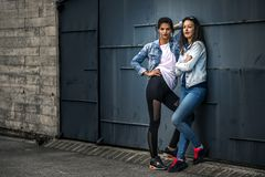 Portrait of two young and attractive women standing next to the wall. Royalty Free Stock Image