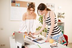 Young beautiful girls thoughtfully looking in book with laptop on table working together in office stock photo