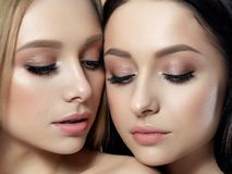 Portrait of two young beautiful women. Closeup portrait of two young beautiful women. Creamy beige colors. Nude makeup. Skin care, cosmetics, SPA therapy or stock photo