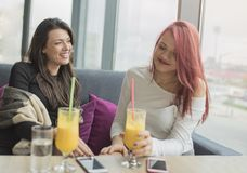 Portrait of two young beautiful women at coffee shop, girl talk. Two young female friends enjoying together in a restaurant laughing, talking and gossiping Stock Images