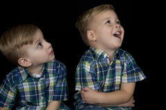 Portrait of two young boys matching shirts looking up away from Stock Images