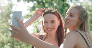 Portrait of two young cheerful girls having fun and making selfie, outdoors. Two beautiful teenage girls using phone in a city park stock video footage