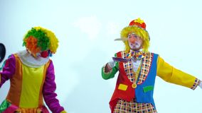 Portrait of two young comic clowns having fun together playing with toy-pans stock video