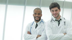 Portrait of two young doctors in medical gown stock video