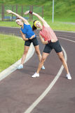 Portrait of Two Young Feale Sportswomen Having Stretching Exercises Outdoors Stock Image