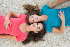 Portrait of two young female friends lying on rug Stock Photos