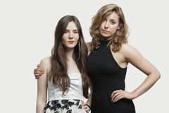 Portrait of two young female friends standing together over gray background Stock Photos