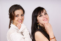 Portrait of two young girls. Portrait of two young women posing side by side with hand under chin. Studio shot Stock Photos
