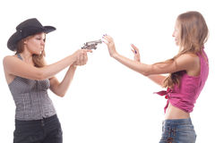 Portrait of two young girls with a gun. Shooting studio Royalty Free Stock Photos