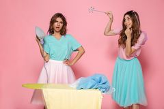 Portrait of a two young girls ironing clothes. On a pressboard while standing with an iron an a magical wand  over pink background Stock Photography