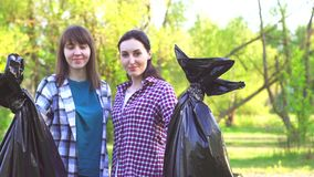 Portrait of two young girls in shirts with plastic bags with garbage in their hands looking at the camera. Portrait of two young sisters girls in shirts in the stock video footage
