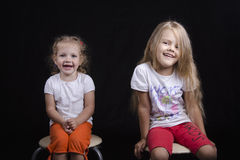 Portrait of two young girls sitting on chairs Royalty Free Stock Photo