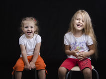 Portrait of two young girls sitting on chairs Stock Photo