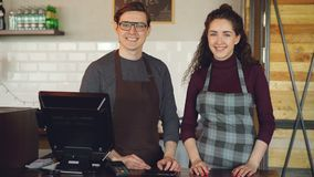 Portrait of two young good-looking waiters standing at cashier`s desk in coffee-house and smiling. Successful business. Portrait of two young good-looking stock footage