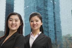 Portrait of two young happy businesswomen outdoors among skyscrapers Royalty Free Stock Photo
