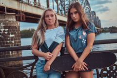 Portrait of a two young hipster girls holds a skateboard and leaning on a guardrail on a background of the old bridge. royalty free stock photos