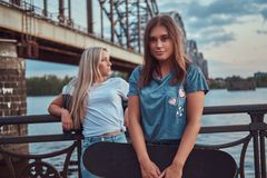 Portrait of a two young hipster girls holds a skateboard and leaning on a guardrail on a background of the old bridge. royalty free stock photography