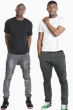 Portrait of two young men in casuals over gray background Stock Photo