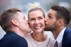 Two young men kissing woman on her cheeks. Portrait of two young men kissing blond women on her cheeks Royalty Free Stock Photo