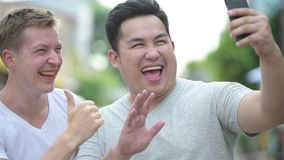 Two young multi-ethnic handsome men together in the streets outdoors. Portrait of two young multi-ethnic handsome men together in the streets outdoors stock footage